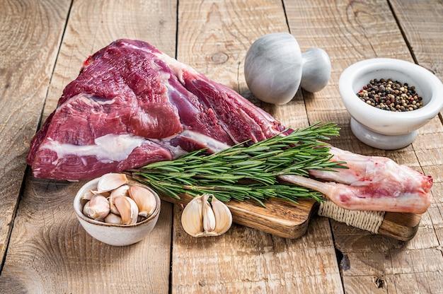 Agneau cru frais ou cuisse de chèvre au romarin et au poivre sur une planche à découper