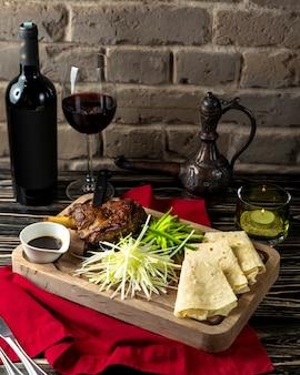 Agneau frit et lavash servi avec du vin rouge