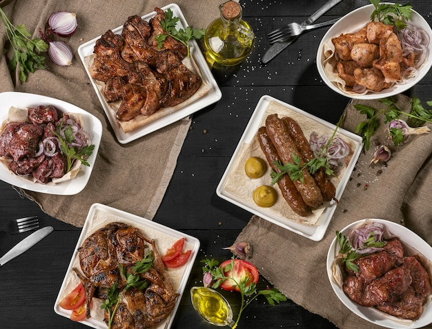 Agneau grillé kebab shashliks poulet tabaka et ailes sur tableau noir
