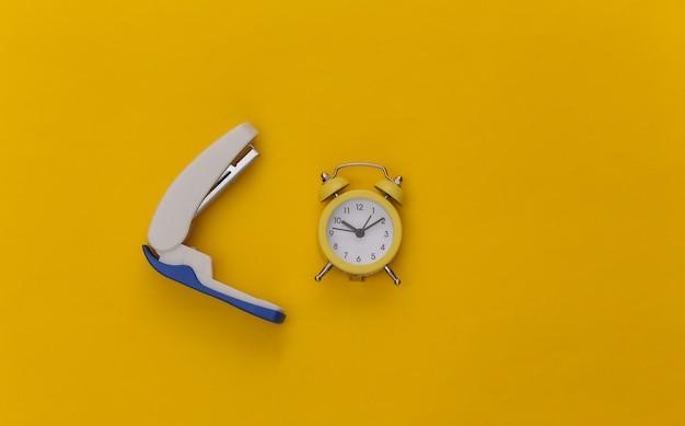 Agrafeuse et réveil sur fond jaune. fournitures de bureau.