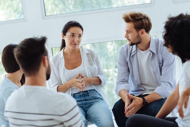 Agréable et agréable thérapeute intelligente regardant son groupe et se préparant à commencer une session tout en étant au travail