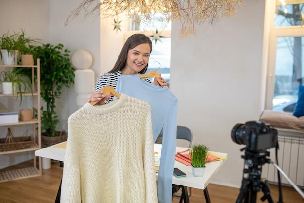 Agréable belle femme debout devant la caméra tout en tenant deux vêtements