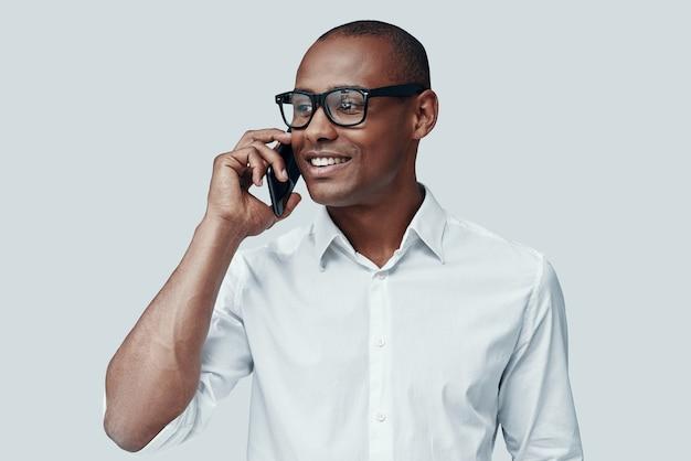 Agréable conversation. beau jeune homme africain parlant au téléphone intelligent en se tenant debout sur fond gris