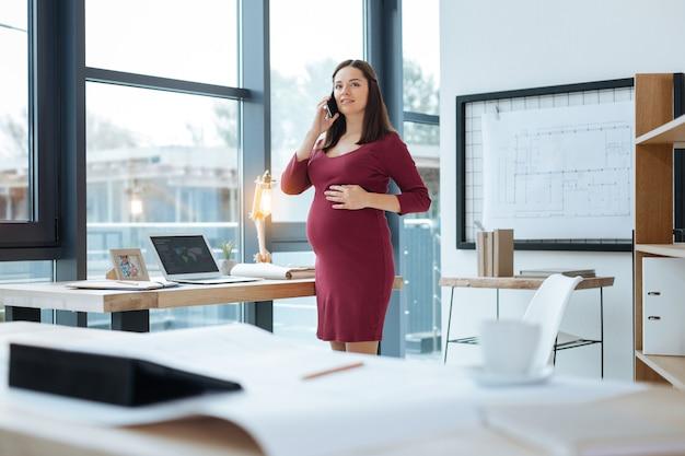 Agréable conversation. jeune femme enceinte debout à la table et à la recherche de suite tout en touchant son ventre et avoir une conversation sur téléphone mobile