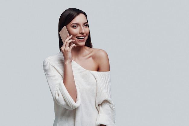 Agréable conversation. jolie jeune femme parlant au téléphone intelligent et souriant en se tenant debout sur fond gris