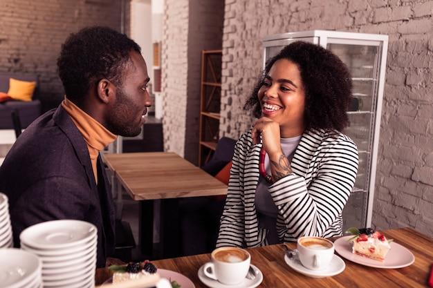 Agréable conversation. joyeux couple positif se parler tout en prenant un café