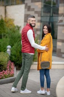 Agréable couple positif se tournant vers vous en se tenant ensemble dans la rue