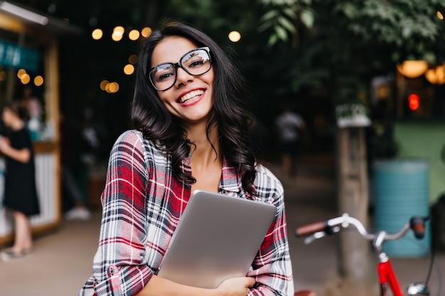 Agréable étudiante internationale posant dans la rue. belle fille brune aux cheveux ondulés tenant un ordinateur portable et en riant.