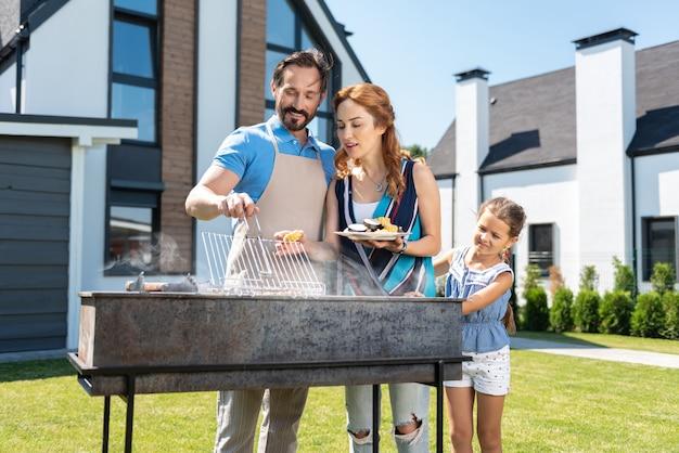 Agréable famille heureuse debout ensemble préparer la viande