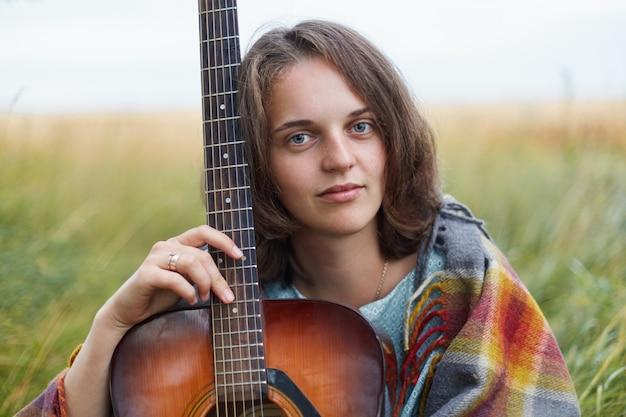 Agréable femme aux yeux bleus charmants et aux cheveux courts noirs assis avec une guitare au champ vert en regardant directement