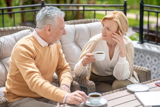 Agréable femme blonde satisfaite et un homme aux cheveux gris assis à côté d'elle à la table pendant une conversation