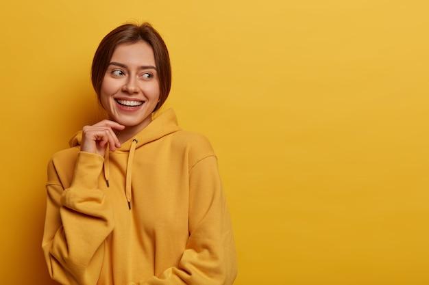 Agréable à la femme caucasienne garde la main sur le visage, détourne le regard avec satisfaction, remarque quelque chose d'agréable, porte un sweat à capuche décontracté, isolé sur un mur jaune, espace vide de côté pour votre promo
