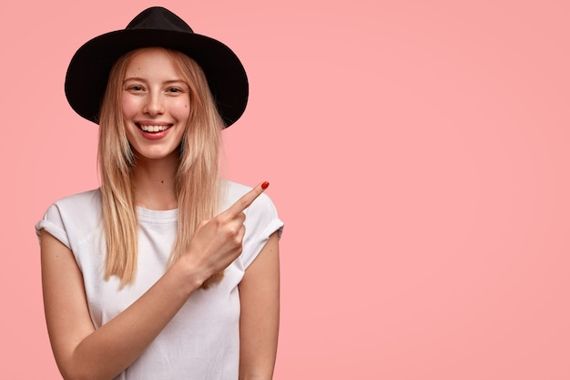Agréable femme européenne avec une apparence attrayante, porte un chapeau et un t-shirt décontracté, souligne