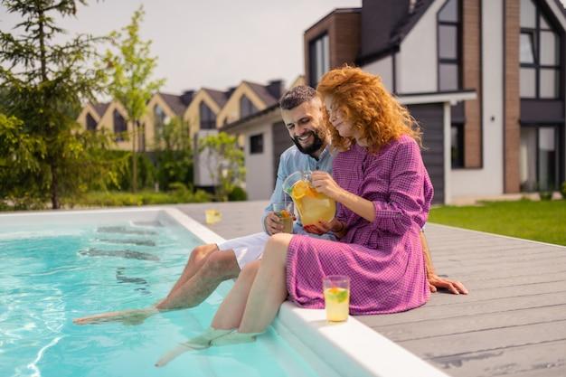 Agréable femme joyeuse verser de la limonade dans l'herbe