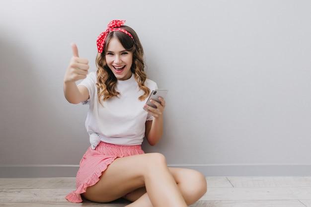 Agréable fille caucasienne avec ruban rouge dans les cheveux noirs, assis sur le sol à la maison. plan intérieur d'un modèle féminin souriant en short rose.