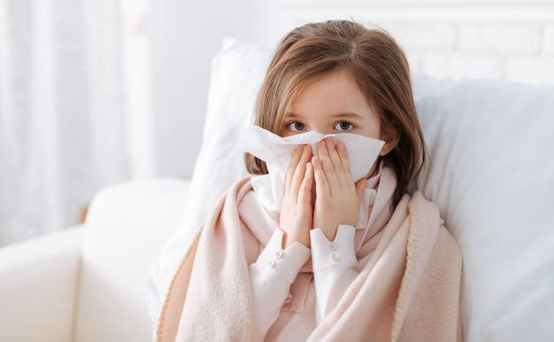 Agréable fille malade tenant un mouchoir et assis sur le canapé tout en se reposant à la maison
