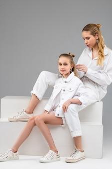 Agréable fille paisible s'appuyant sur sa sœur aînée pendant qu'elle s'occupe de ses longs cheveux sains