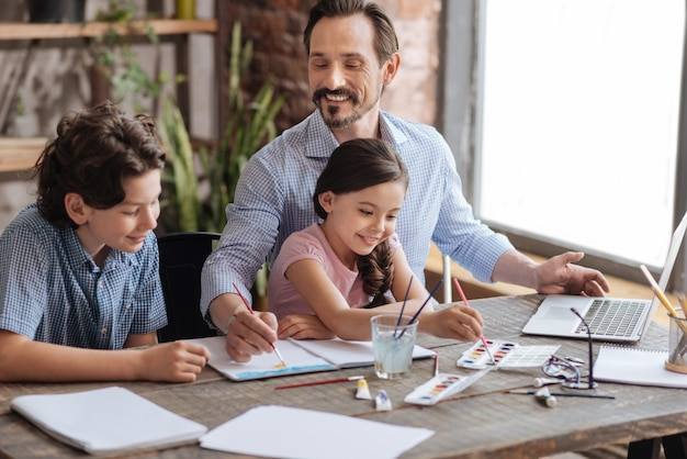 Agréable garçon souriant regardant son père appliquer des traits sur l'aquarelle tandis que sa petite soeur choisit une nouvelle couleur