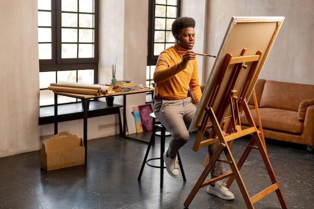Agréable homme créatif tenant un pinceau dans ses mains tout en créant une peinture avec