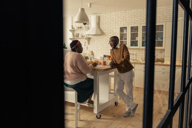 Agréable interaction. beau couple agréable parlant dans la cuisine tout en prenant le petit déjeuner