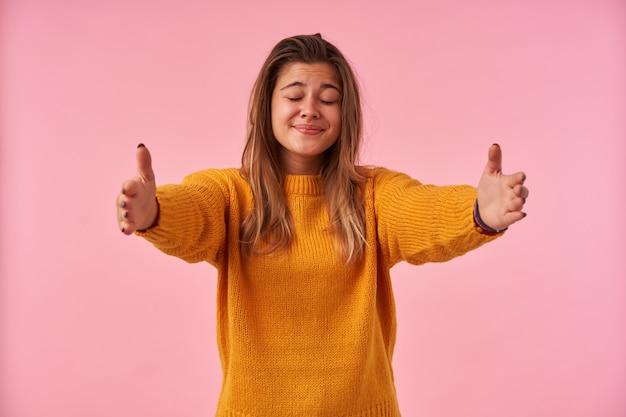 Agréable à la jeune femme aux cheveux bruns gardant les yeux fermés tout en souriant positivement, écartant ses mains levées tout en posant sur rose dans des vêtements décontractés