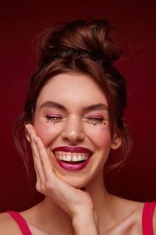 Agréable à la jeune femme aux cheveux bruns heureux avec des lèvres bordeaux et des étoiles d'argent sur son visage tenant la paume sur la joue et riant joyeusement les yeux fermés, isolé