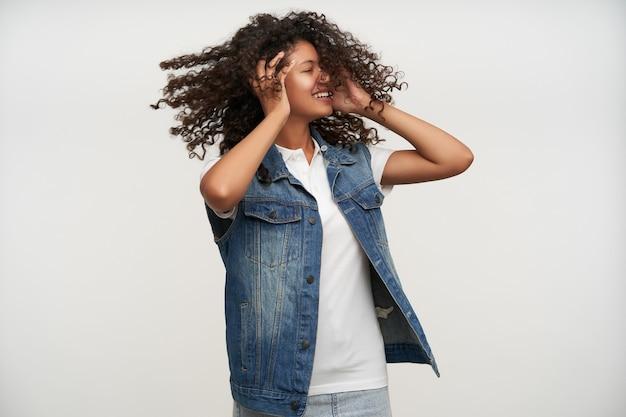 Agréable à la jeune femme frisée aux cheveux longs à la peau sombre tournant la tête et gardant les yeux fermés, souriant joyeusement tout en posant sur blanc avec les mains levées