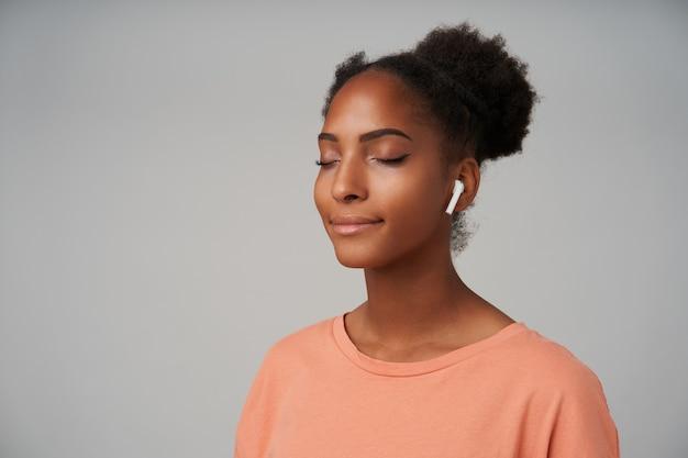 Agréable à la jeune femme frisée à la peau foncée heureuse avec une coiffure chignon souriant volontiers avec les yeux fermés tout en écoutant de la musique avec des écouteurs, isolé sur fond gris