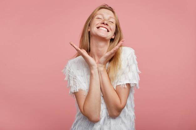 Agréable à la jeune femme joyeuse avec des cheveux foxy gardant les mains levées sous sa tête et souriant largement les yeux fermés, vêtu d'un t-shirt festif blanc tout en posant sur fond rose