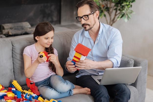Agréable jeune père assis sur le canapé et montrant la maison en bloc à sa fille bien-aimée alors qu'elle tient un modèle de voiture et regarde la maison avec le sourire