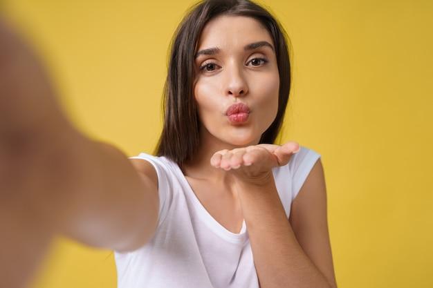 Agréable jolie fille faisant selfie en studio et riant. belle jeune femme aux cheveux bruns se prenant en photo sur fond jaune vif.
