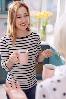 Agréable pause café. l'accent étant mis sur une agréable jeune femme buvant du café avec sa mère senior et bavardant avec elle joyeusement