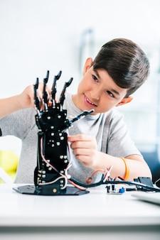 Agréable petit garçon ingénieux profitant de ses cours d'ingénierie tout en testant la tête humanoïde robotique