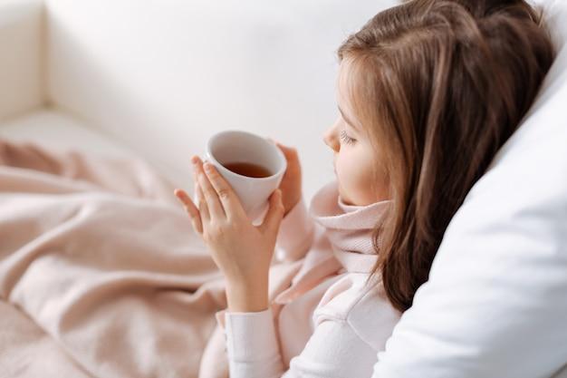 Agréable petite fille fatiguée, boire du thé et se reposer à la maison tout en se sentant malade