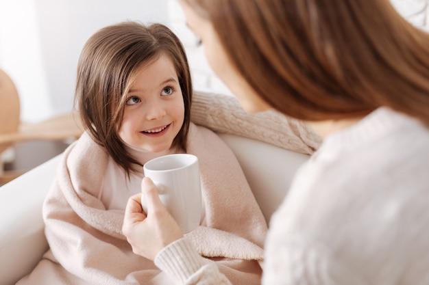 Agréable petite fille joyeuse souriant et regardant sa mère tout en se remettant de la grippe