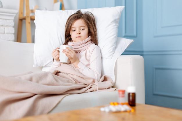 Agréable petite fille malade couchée dans son lit et boire du thé tout en regardant des médicaments