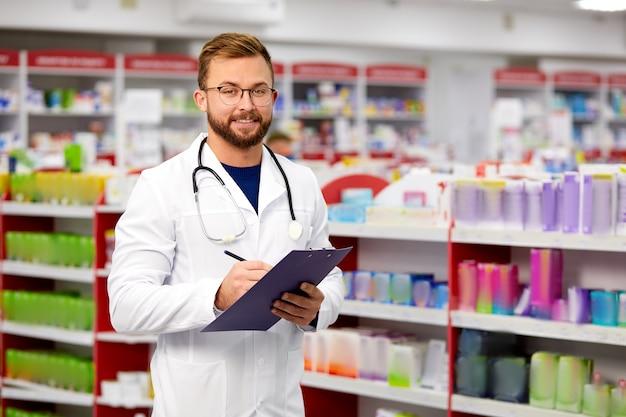 Agréable pharmacien masculin écrit sur le presse-papiers à la pharmacie
