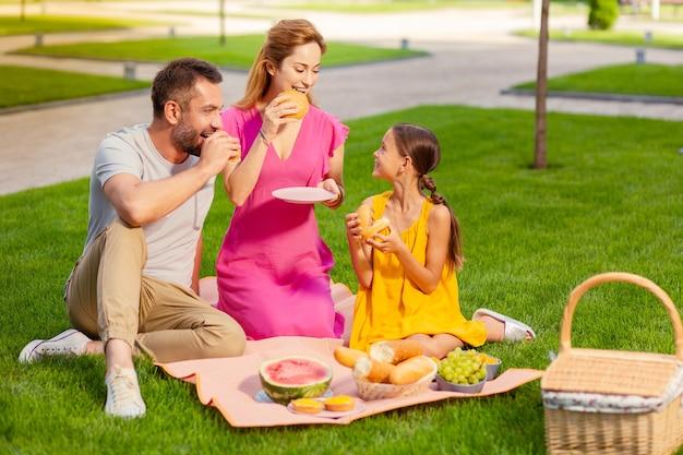 Agréable pique-nique. famille unie positive ayant un pique-nique tout en passant le week-end ensemble