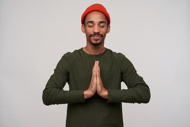 Agréable à la recherche de jeune mec brune à la peau sombre barbu levant les mains en geste de prière tout en posant sur blanc, gardant les yeux fermés et souriant légèrement