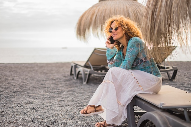 Agréable et sourire beau modèle de femme d'âge moyen 40 ans européen avec des cheveux bouclés dorés parlant au téléphone avec des amis ou des parents comme fils ou mari s'asseoir à la plage de plein air