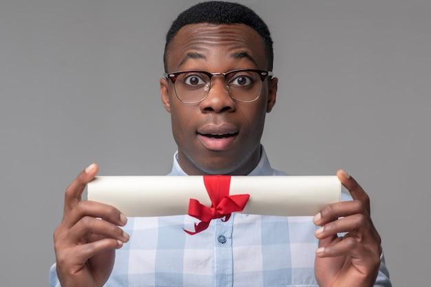 Agréable surprise. joyeux afro-américain surpris dans des verres et chemise légère montrant du papier attaché avec un ruban rouge
