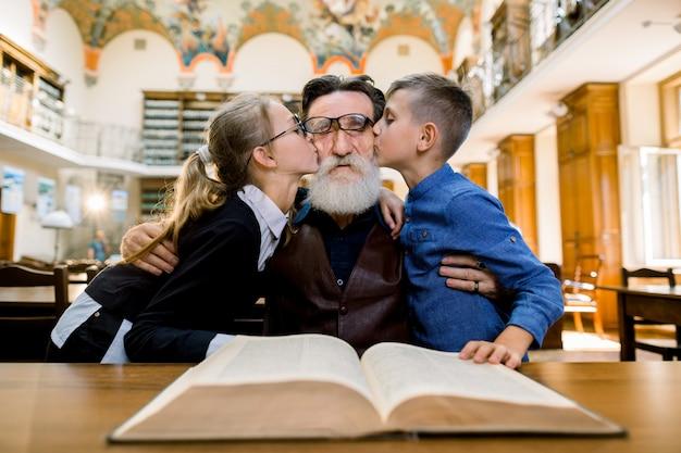 Agréable vieux grand-père barbu passant du temps dans la bibliothèque avec sa petite-fille et son petit-fils, l'embrassant dans les joues