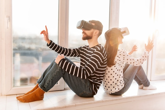 Agréable week-end. couple fabuleux fasciné excité se détendre sur le rebord de la fenêtre tout en portant des casques vr et des têtes mobiles