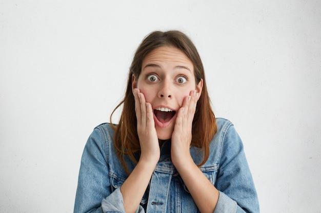Agréablement surpris femme à la recherche avec les yeux bugged tenant la main sur les joues ouvrant sa bouche