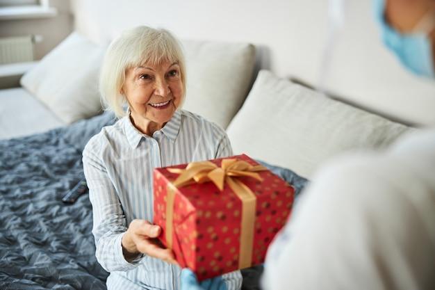 Agréablement surpris personne vieillissante saisissant une boîte à l'intérieur d'un papier d'emballage d'une femme de soins à domicile
