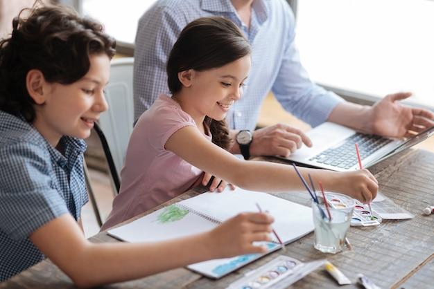 Agréables enfants heureux assis à la table et peignant une aquarelle ensemble pendant que leur père travaille sur l'ordinateur portable