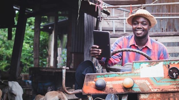 Agriculteur africain recherchant et enregistrant des détails sur la tablette avec assis sur un tracteur dans une ferme de vaches. concept d'agriculture ou de culture