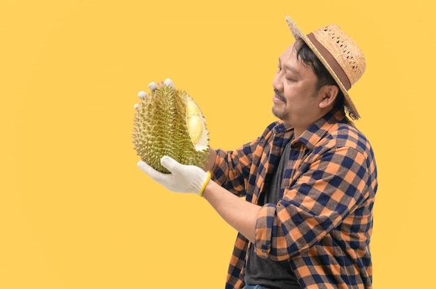 Agriculteur d'âge moyen en regardant leur durian et fier de leurs propres produits isolés