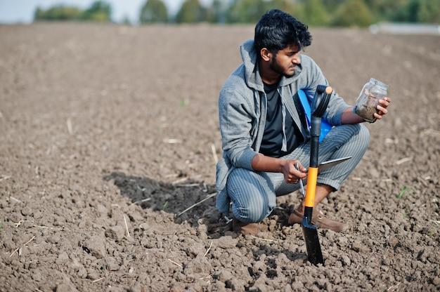 Agriculteur agronome sud-asiatique avec pelle inspectant le sol noir. concept de production agricole.