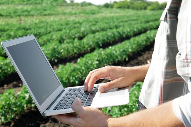 Agriculteur à l'aide d'un ordinateur portable dans le champ